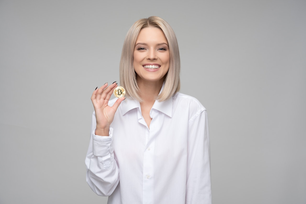Woman smiling while holding bitcoin