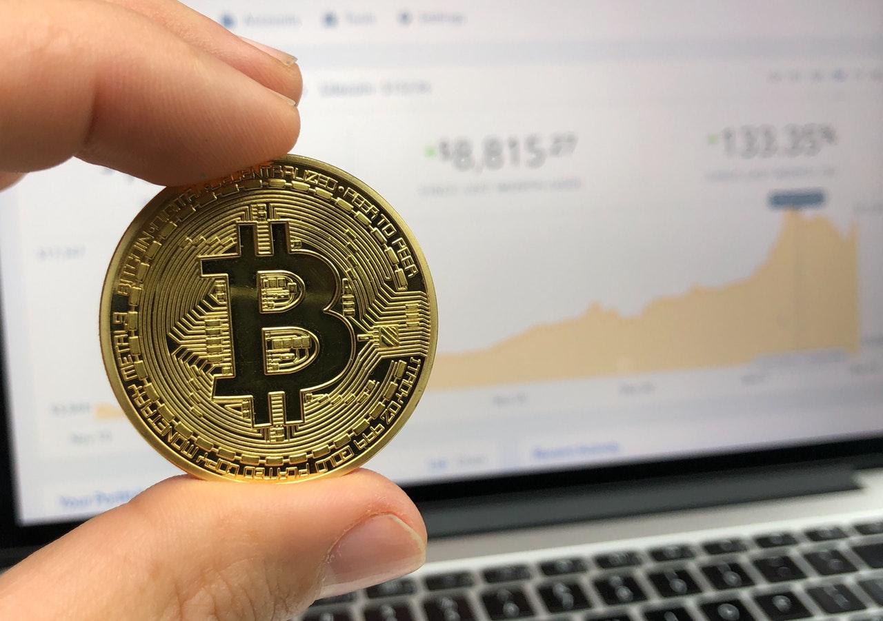 Man holding a gold bitcoin