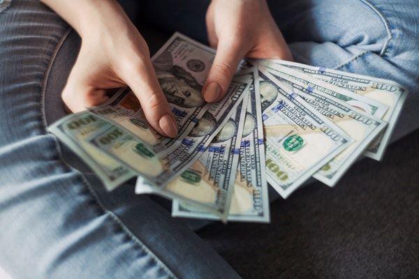 adult holding cash money